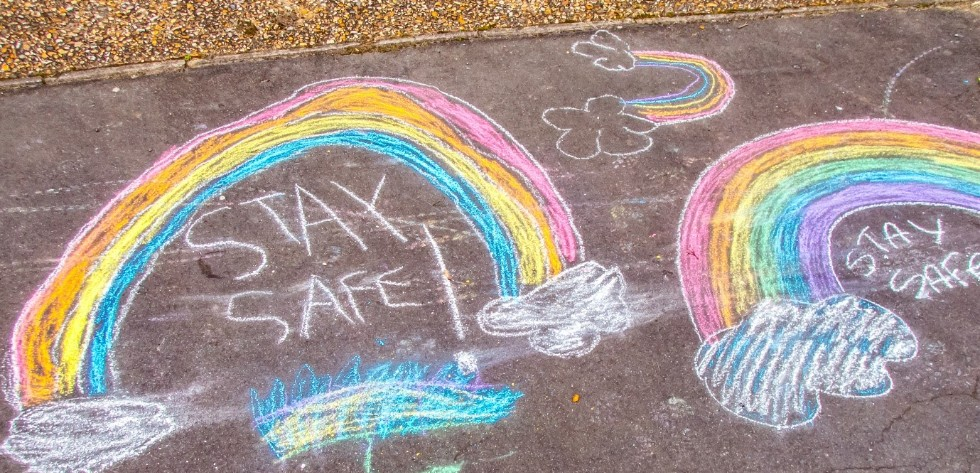 rainbows drawn on the pavement using coloured chalk
