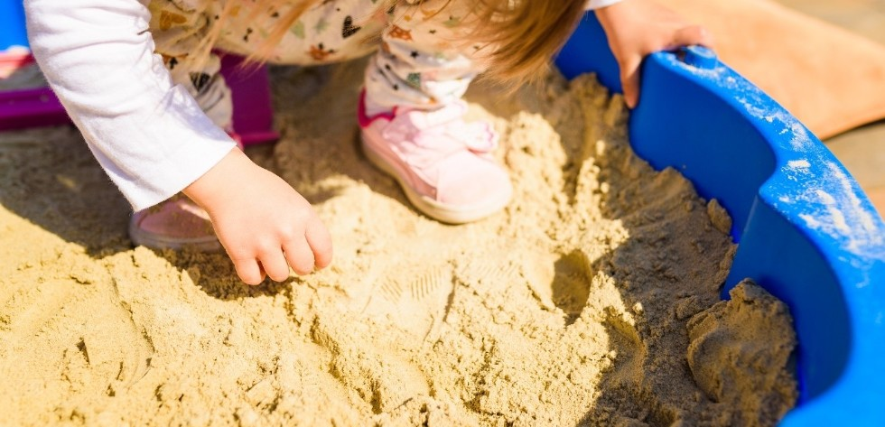 young child playing in sandbox