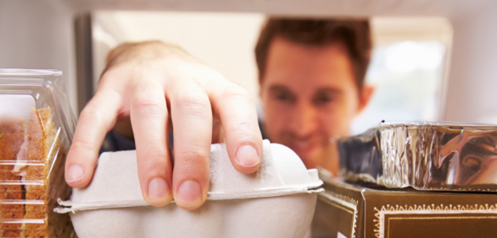 Man reaching into a fridge for some eggs