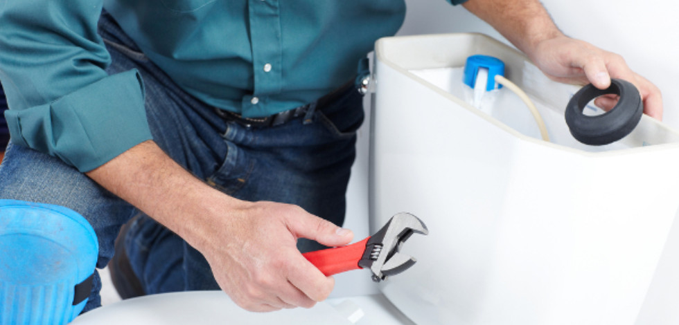 Plumber kneeling by a toilet holding a washer