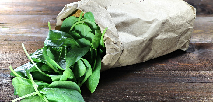 Paper bag of spinach leaves