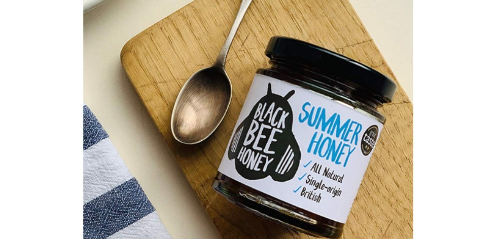 Pot of Black Bee Honey on a chopping board next to a spoon