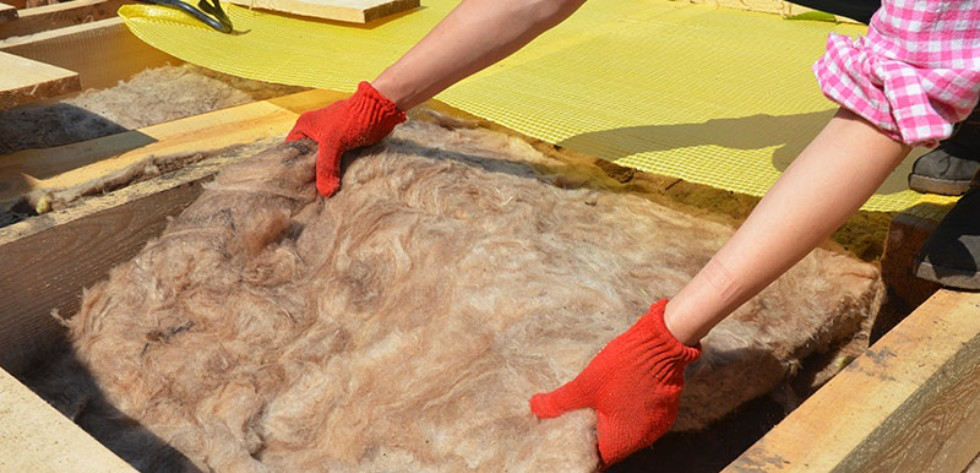 image of someone placing insulation into a floor