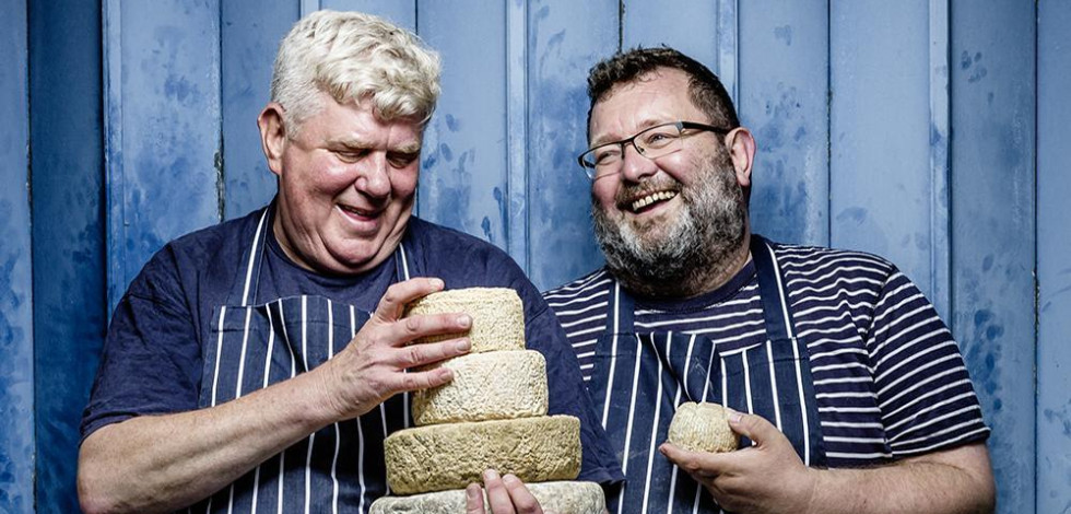 Two men holding artisan cheeses