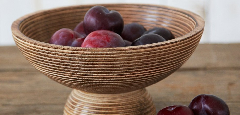 Carved wooden bowl filled with plums