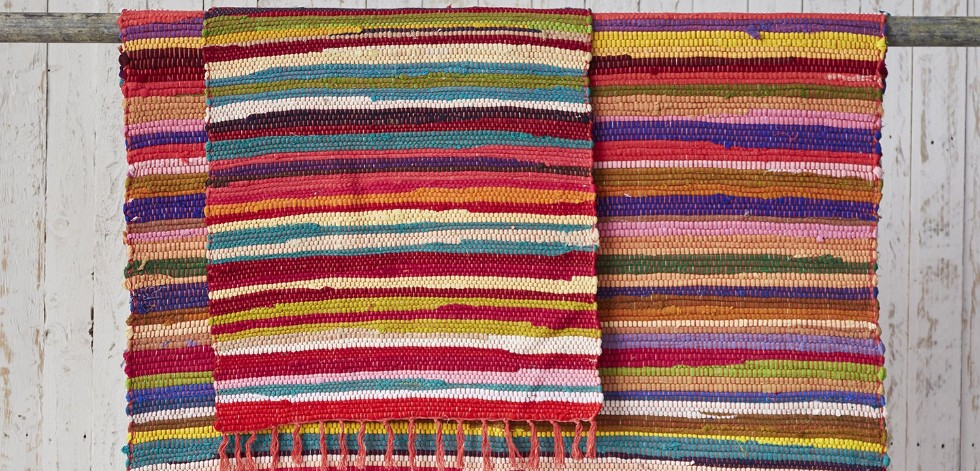 Two multicoloured rugs hanging over a rail