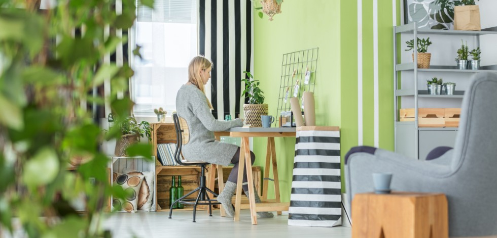 Woman working in a plant-filled home office