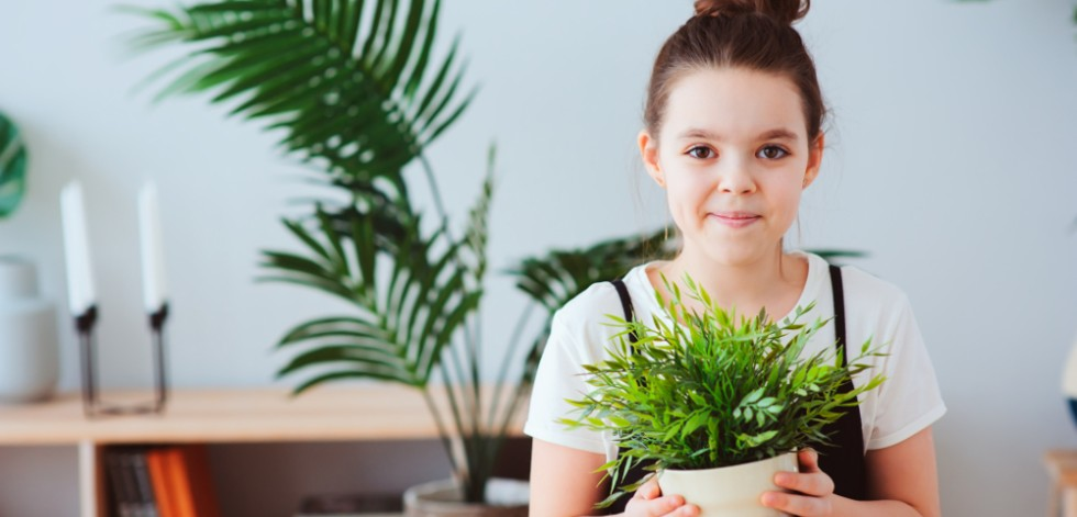 Teenage girl holding a pot plant