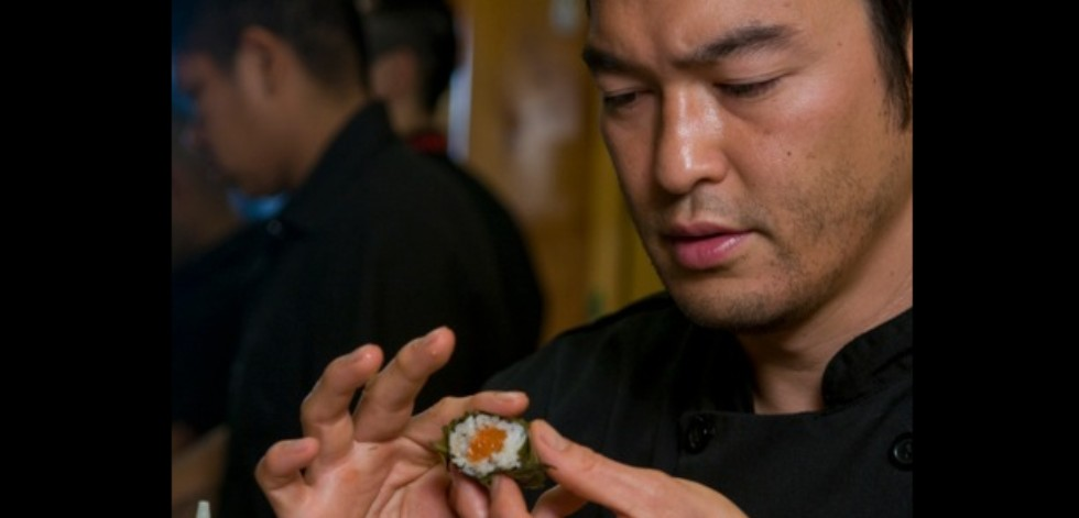 Chef Bun Lai rolling a piece of sushi