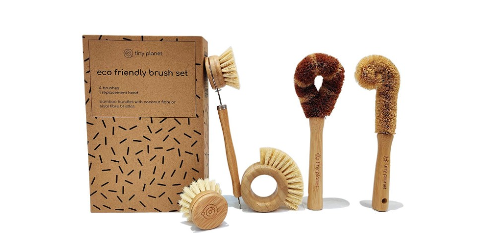 A photograph of five cleaning brushes of different shapes and sizes, made from bamboo with sisal grass and coconut fibre bristles, next to the cardboard packaging