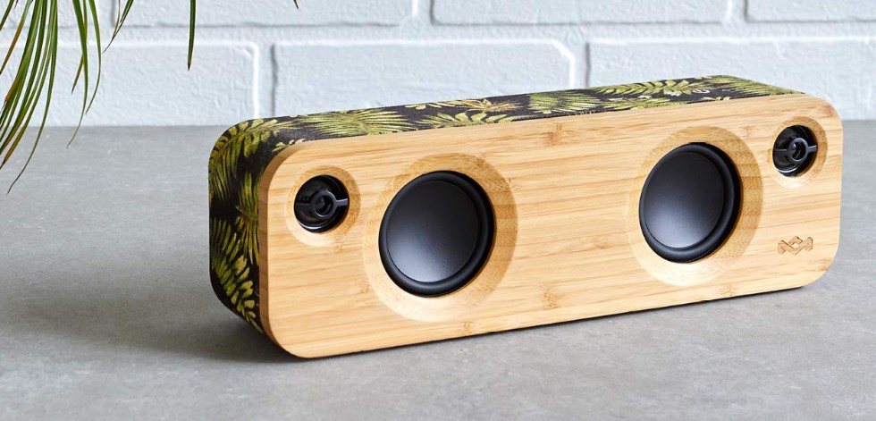 Photograph of a portable speaker, low and rectangular, with a carved bamboo face plate and fabric-covered back