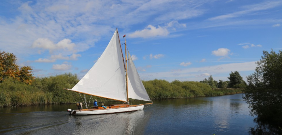 Photograph of a small sailing boat with three people aboard, sailing up a quiet reed-banked channel in the Norfolk Broads