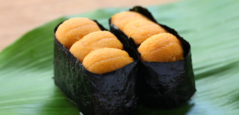 A photograph of six 'sushi uni' on a banana leaf. These are sushi rice wrapped in seaweed and topped with bright orange meat from sea urchins.
