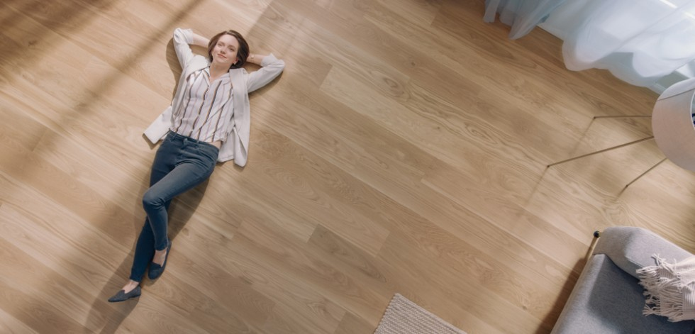 Woman lying on the floor in a very tidy room