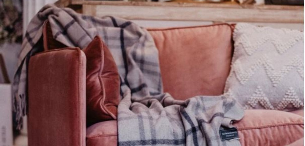 A grey tartan blanket thrown casually over the corner of a pink velvet sofa
