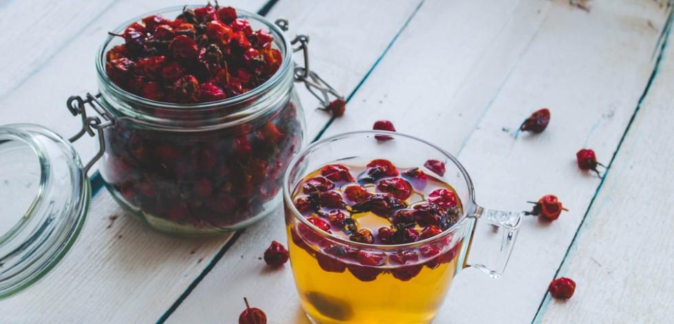 A pot of dried rose hips next to a cup of brewed rose hip tea