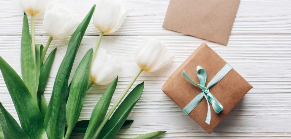 White tulips and brown paper wrapped gift with ribbon