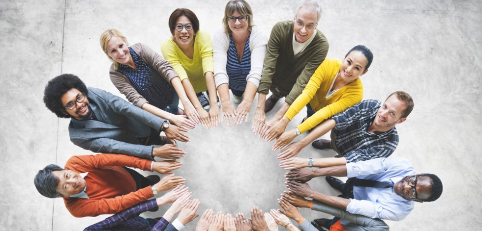 A diverse group of adults standing in a circle with their hands stretched towards the centre