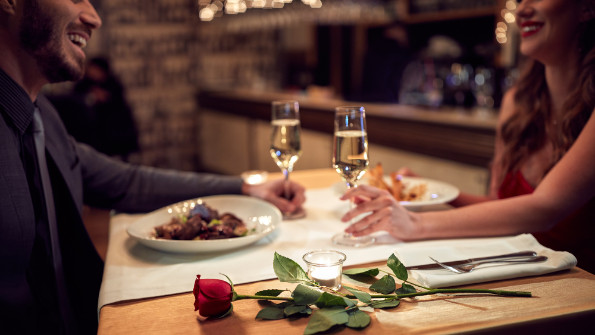 Man and woman holding hands over a candlelit restaurant table