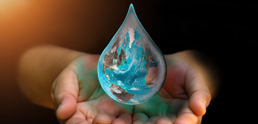 a drop of water reflecting the world in a pair of hands