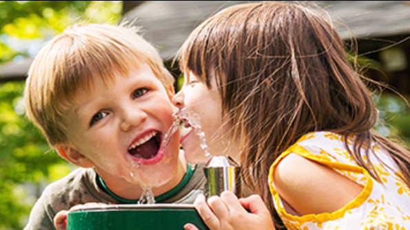 Children drinking at a water fountain