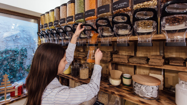 Woman dispensing lentils in a zero waste shop